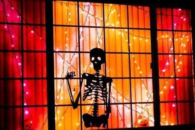 скелет в окне на Хэллоуин